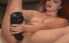 Redhead Julia rides a black brutal dildo