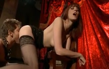 Red haired dominatrix playing with her slave